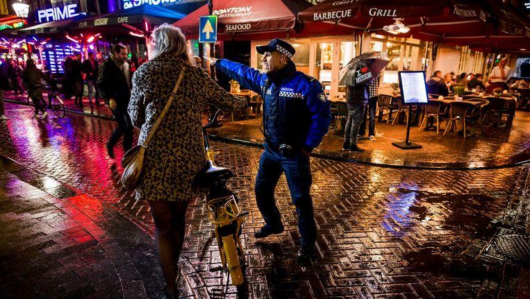 Een Amsterdamse handhaver aan het werk in de avond. Beeld Rink Hof