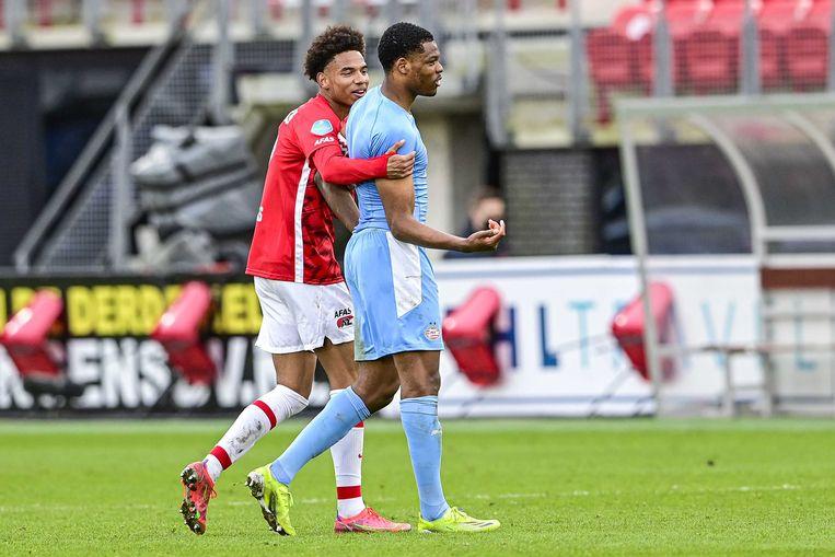 Calvin Stengs (AZ) slaat een arm om Denzel Dumfries (PSV) tijdens de wedstrijd tussen AZ en PSV in het AFAS stadion in Alkmaar. AZ won met 2-0. Beeld ANP