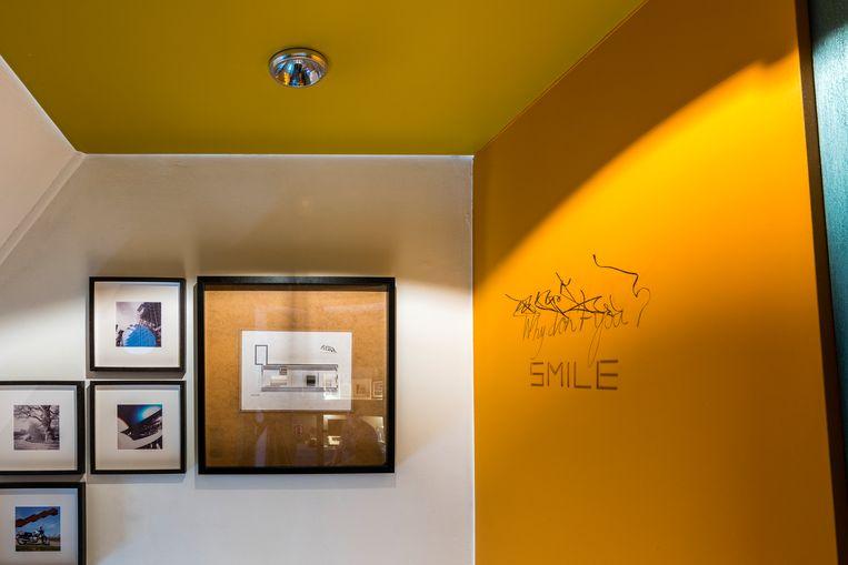 De muur in de traphal is als een eregalerij voor de zelfgemaakte foto's en collages van Huub.Bovenaan de trap hangt het kunstwerk 'Why don't you' van Fred Eerdekens.Als ludieke twist voegde hij het woordje 'smile' eraan toe. Beeld Luc Roymans