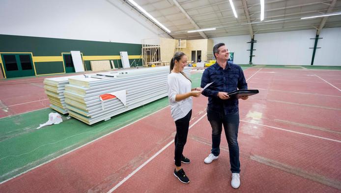 """Kevin en Maryam van der Heem op een van de overbodige tennisbanen waar een enorm speelparadijs moet verschijnen: """"Groen, wit, oranje en diverse geeltinten voeren de boventoon.''"""