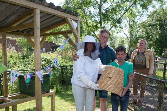 Gedeputeerde Anita Pijpelink heeft het bijenhotel op de Stadsboerderij in Zierikzee geopend, samen met verzorgers Arjan Krab (r) en Ad de Jonge (midden).