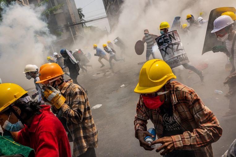 Anti-coup-demonstranten reageren nadat de oproerpolitie traangas heeft afgevuurd om hen  in Yangon, Myanmar te verspreiden. De militaire regering van Myanmar heeft de afgelopen dagen het harde optreden tegen demonstranten geïntensiveerd door traangas en scherpe munitie te gebruiken, demonstranten en journalisten aan te vallen en te arresteren.  Beeld Photo by Hkun Lat/Getty Images