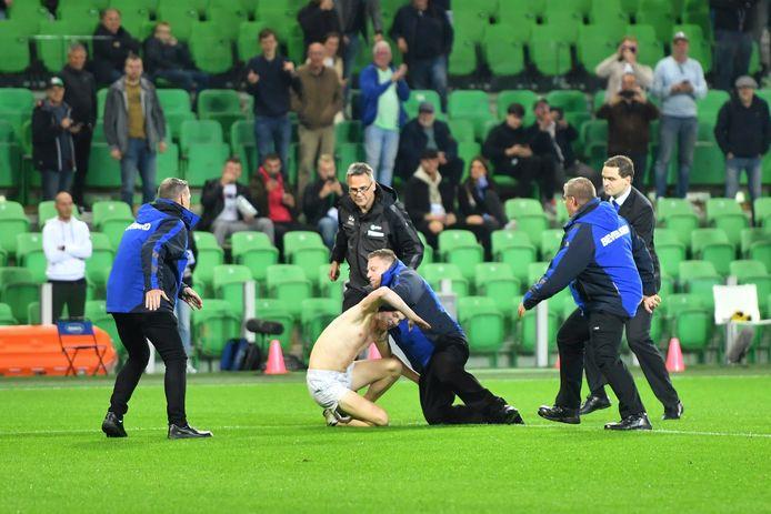 De stewards overmeesteren één van de veldbestormers tijdens FC Groningen - Vitesse.