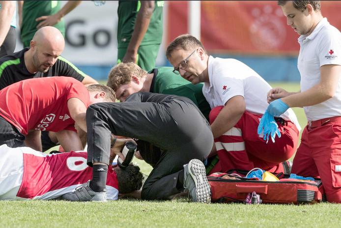 Ajax-speler Abdelhak Nouri ligt op de grond tijdens het oefenduel met Werder Bremen waar hij last kreeg van hartritmestoornissen.