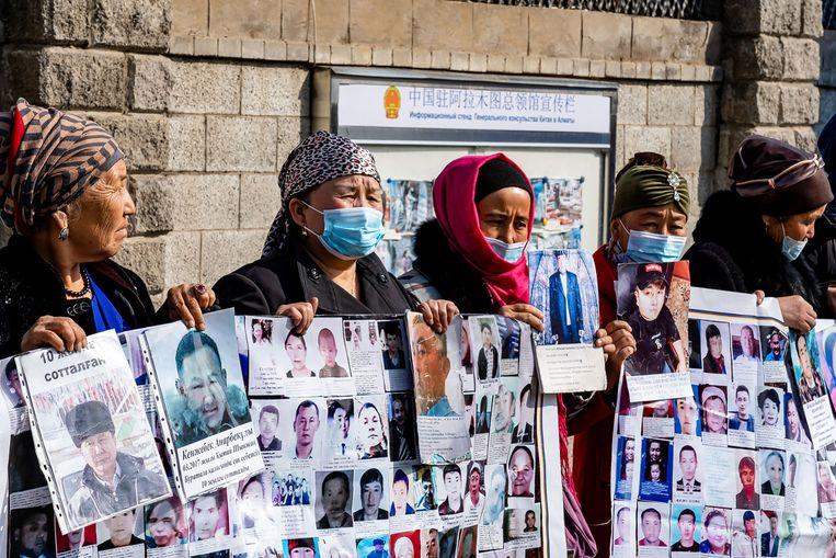 Vrouwen demonstreren aan het Chinese consulaat in Kazachstan om de detentie van hun echtgenoten aan te klagen.  Beeld AFP