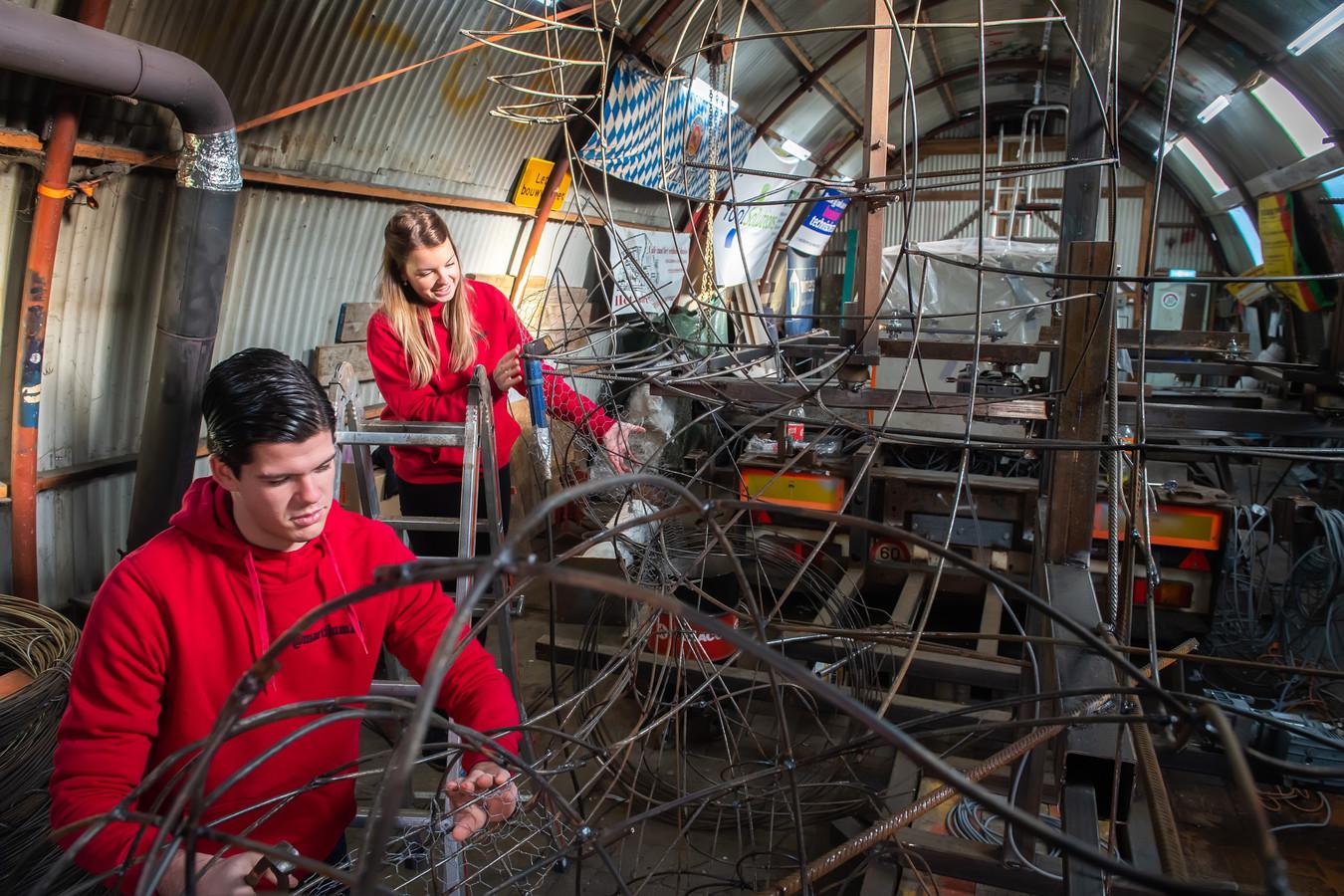 Martijn Meeuwissen en Freeke van Gils aan het werk in de bouwhal van CV Piendraod in Prinsenbeek.