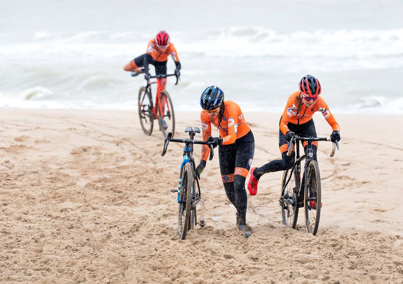 Lucinda Brand (blauwe helm) en Denise Betsema met op de achtergrond de opkomende Annemarie Worst op het strand van Oostende. Beeld Klaas Jan van der Weij / de Volkskrant