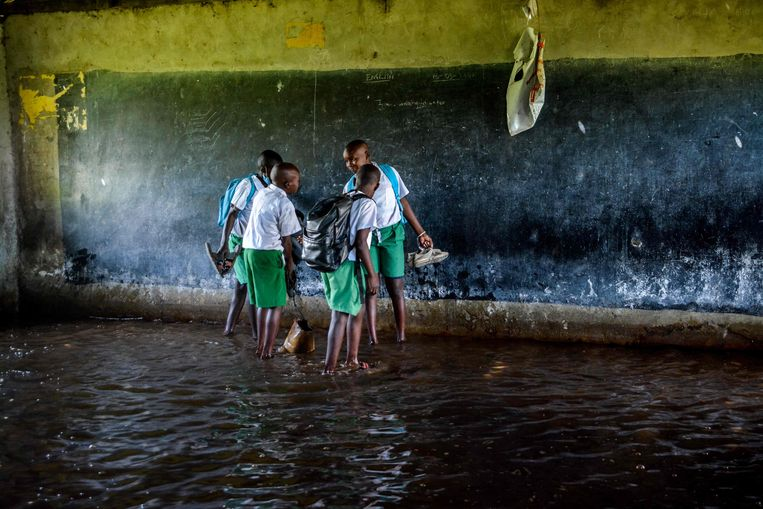 Heel fijn dat de scholen weer opengaan in Kenia, na een lange lockdown om het coronavirus te bestrijden. Maar dan schiet het niet op als ondertussen het Victoriameer overstroomt, zoals deze scholieren merken in hun ondergelopen klaslokaal in de stad Kisumu.  Beeld AFP