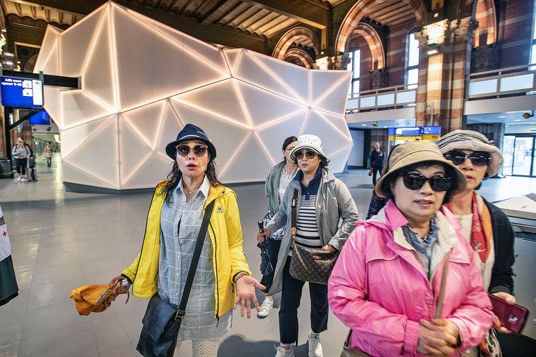 Toeristen lopen door een lege hal van het Centaal Station in Amsterdam.   Beeld Guus Dubbelman / de Volkskrant