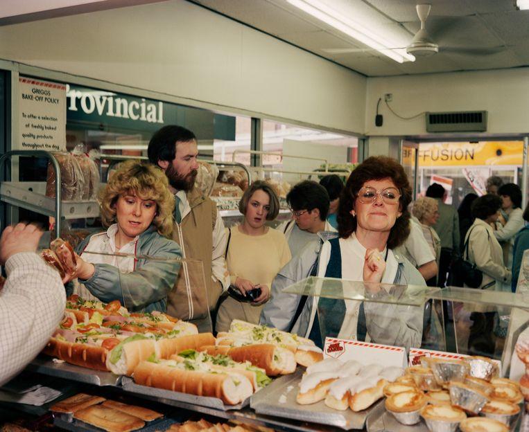 Een gezond broodje of toch maar...Moeilijk kiezen uit al dat lekkers in Greggs Bakery, Salford, in 1986. Beeld ©Martin Parr / Magnum Photos
