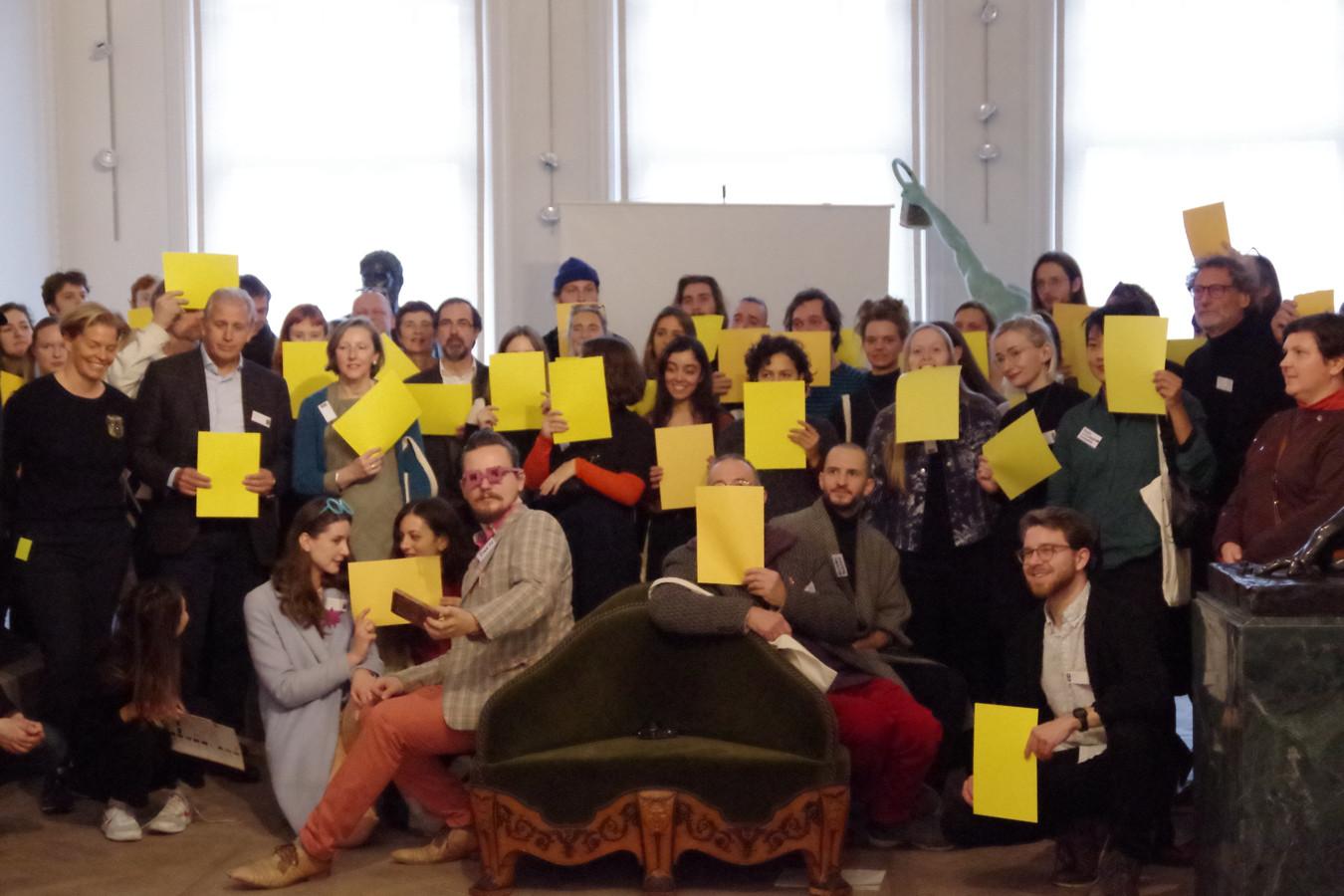 De deelnemers protesteren ook tegen de verlaging van de projectsubsidies door een geel blad voor hun gezicht te houden