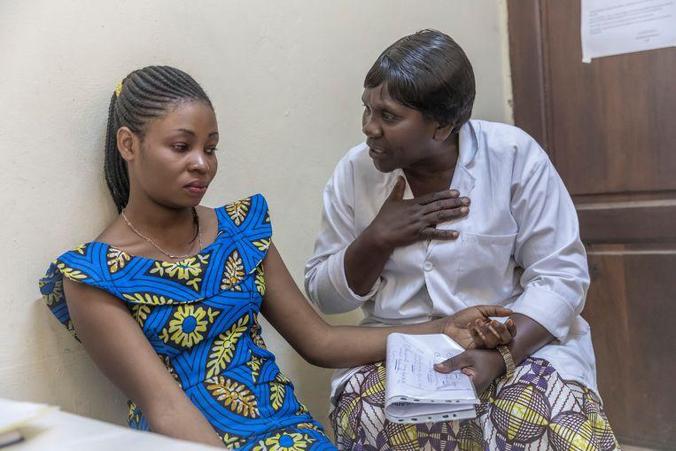 Marie Kashongwe (21) wordt getroost door Madam Cherie, een sociaal hulpverlener in het Panzi ziekenhuis.  Beeld Sven Torfinn / de Volkskrant