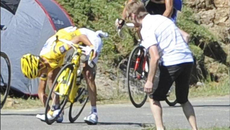 Een vloekende Andy Schleck staat te voet op Port de Balès met een vastgelopen ketting. Hij zal 39 seconden verliezen, en het geel. Beeld UNKNOWN