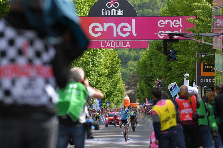 Pello Bilbao passeert in de volgelopen straten van L'Aquila, waar nog steeds veel onaf is, als eerste de finish.  Beeld Getty Images