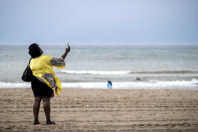 Een strandgangster trotseert vorige maand de wind op het strand van Scheveningen.