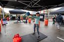 """Marianne van Sommeren doet aan hardlopen. Ze is blij met deze motiverende aanvulling onder  een partytent bij Indoor Action in de open lucht. Ze kan nu ook met de gewichten aan de slag van de sportschool. ,,Je kunt thuis natuurlijk ook werken met flessen  gevuld met water maar dat is toch anders."""""""