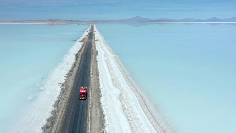 Een vrachtwagen op de weg door het zoutmeer van Uyuni in Bolivia.