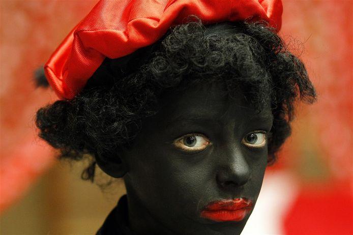 Kind geschminkt als zwarte piet op archiefbeeld.