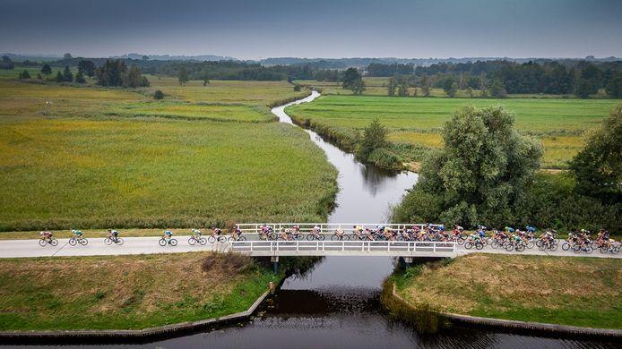 Het peloton in de Omloop Noordwest Overijssel over de bruggen van de Arembergergracht. Nationaal Park De Wieden op de achtergrond.