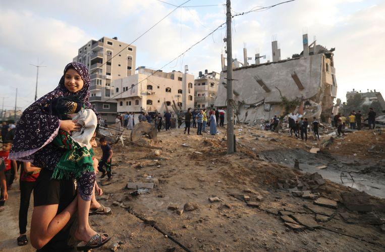 Een Palestijnse man draagt zijn dochter op zijn schouder in de stad Beit Lahia in Gaza. Gebouwen zijn er verwoest door Israëlische luchtaanvallen.  Beeld AFP