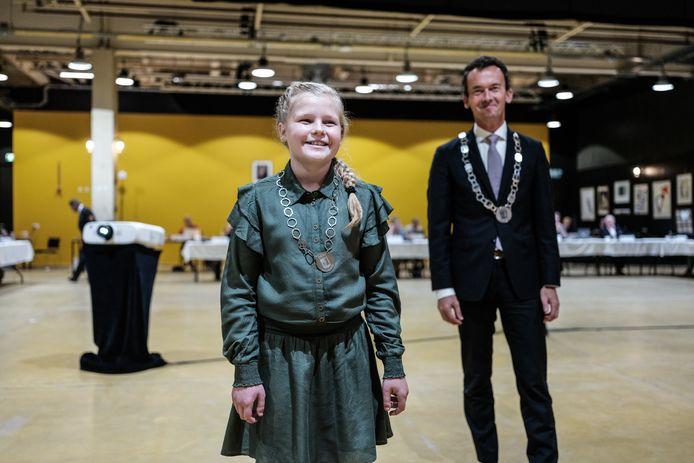 Kinderburgemeester Jasmijn Braam tijdens de raadsvergadering waar zij werd benoemd door burgemeester Lucien van Riswijk, rechts achter haar.