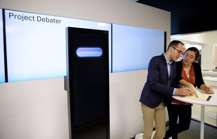 Links Project Debater, de IBM-computer met dossierkennis waar Tweede Kamerleden jaloers op zijn. Rechts topdebater Dan Zafrir, die zich voorbereidt op een debat met de zwarte kast naast hem op het kantoor van IBM in San Francisco. Beeld AP