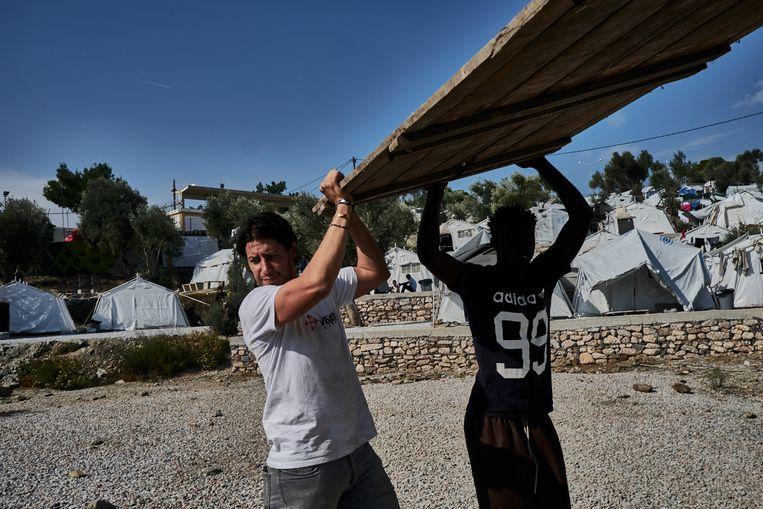 Adil Izemrane  en een inwoner van Olive Grove halen een container leeg. Beeld Joris van Gennip