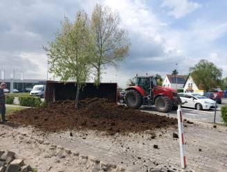 Kar van tractor kantelt op rotonde, mest ligt op de stoep verspreid