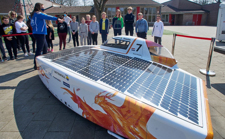 Caroline Smulders (vooraan met blauw jack) van het studententeam TU Delft laat de Nuna auto zien aan de leerlingen van groep 7-8 van basisschool De Kiem in Heesch.