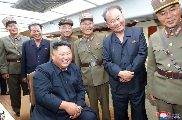 De Noord-Koreaanse leider Kim Jong Un (zittend) is aanwezig bij het testen van een nieuw wapen op een geheime locatie in Noord-Korea.  Beeld AFP