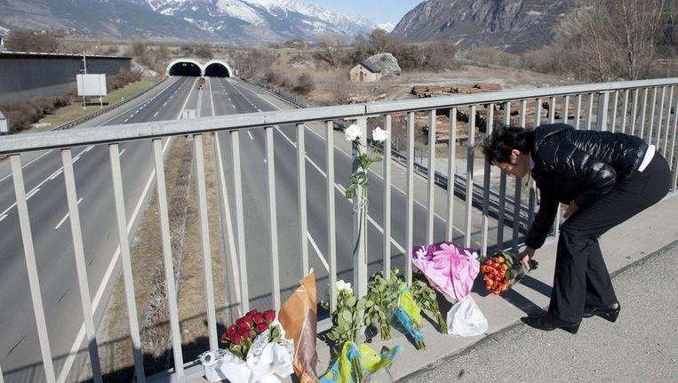 Een vrouw legt bloemen vlakbij de tunnel waar het ongeluk plaatsvond. Beeld null