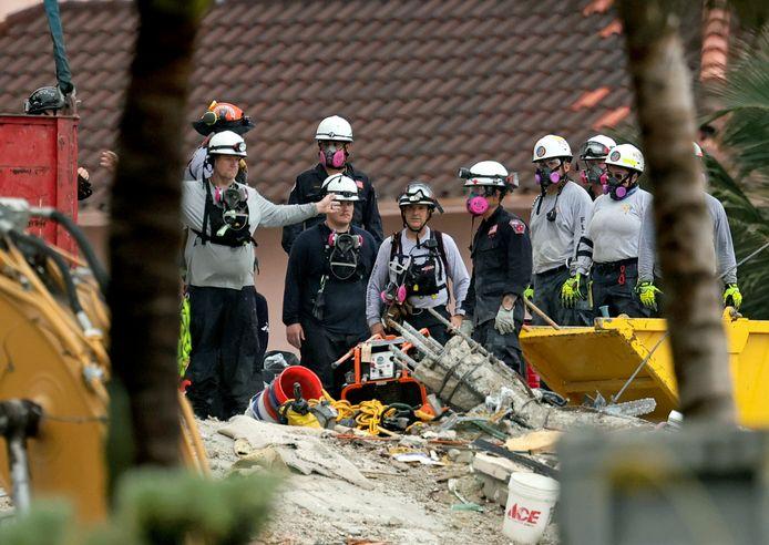 Reddingswerkers tussen het puin van het ingestorte gebouw.