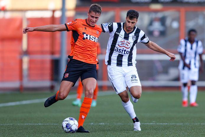Micky van de Ven in duel met Heracles-speler Sinan Bakis.