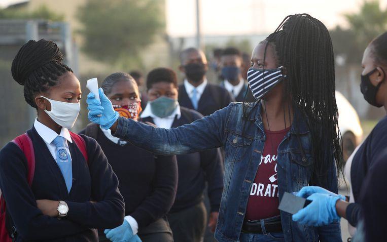Een docent in Kaapstad temperatuurt de leerlingen nu de scholen na de lockdown weer opengaan. Beeld Reuters