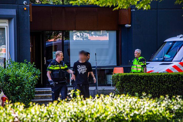 De man die ervan wordt verdacht zijn kamergenoot te hebben doodgestoken wordt naar buiten gebracht bij De President in Velp.