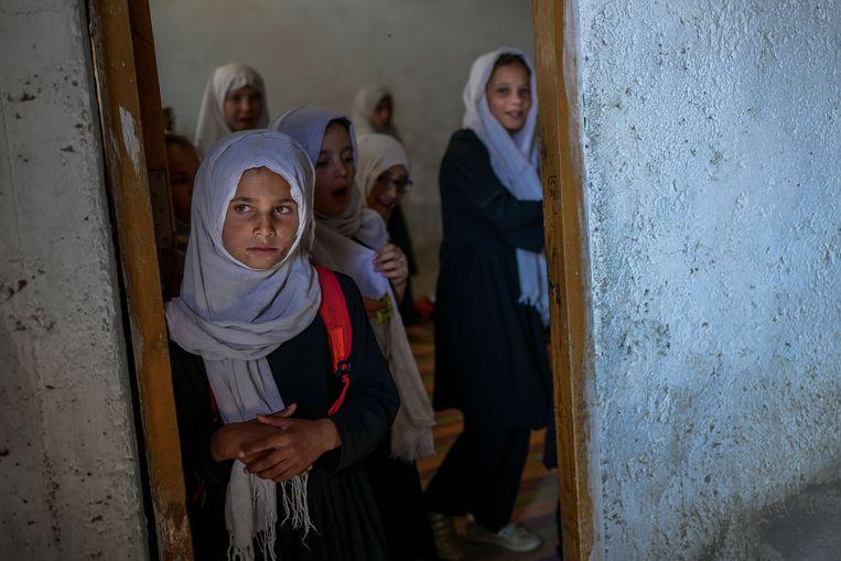 Meisjes komen aan bij hun klaslokaal in een school in Kabul. Het ministerie van onderwijs riep jongens en mannelijke leraren vandaag op zaterdag naar school te gaan. Dat er over meisjes en vrouwen niets gezegd werd stemt weinig hoopvol over toekomstig onderwijs voor vrouwen. Beeld AFP