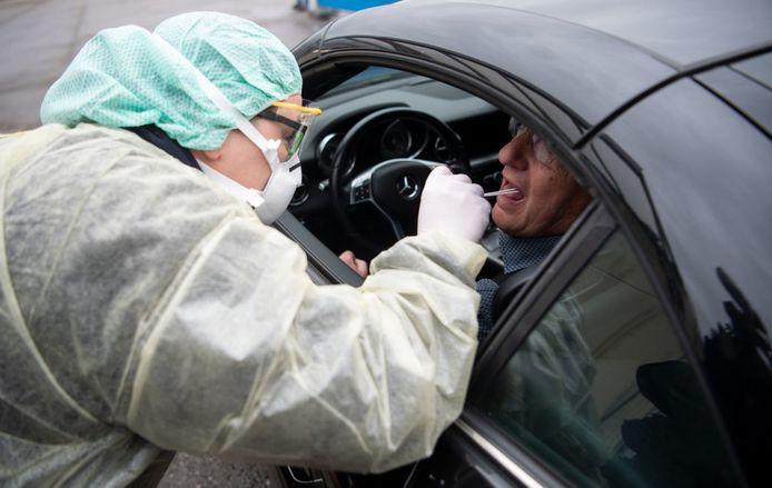 Een patiënt wordt getest op corona via een drive-in in Duitsland.