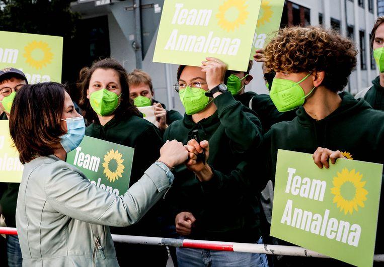 Aanhangers van de Groenen begroeten hun lijsttrekker, Annalena Baerbock, voorafgaand aan het tv-debat van afgelopen zondag. Beeld EPA