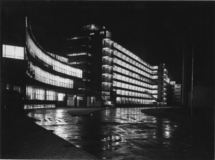 Het kantoor en fabrieksgebouwen van Van Nelle bij avond, vereeuwigd vanaf de ingang van het fabrieksterrein.