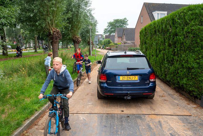 Fietsende schoolkinderen worden door gewone auto's en bouwverkeer om de haverklap in de berm gedwongen. De rijplaten zijn vaak glad en leveren gevaarlijke situaties op.