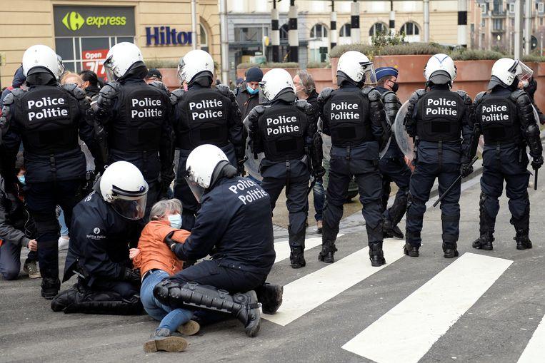 Een manifestant wordt klemgehouden en gearresteerd in Brussel. Beeld REUTERS