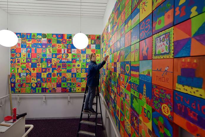 Langzaam maar zeker krijgt het gigantische kunstwerk '750 Roosendalers in kleur' vorm. De panelen met daarop tientallen canvassen worden een voor een in het trappenhuis van het theater bevestigd. Quintus zelf werkt de schilderijtjes hier en daar nog wat bij.