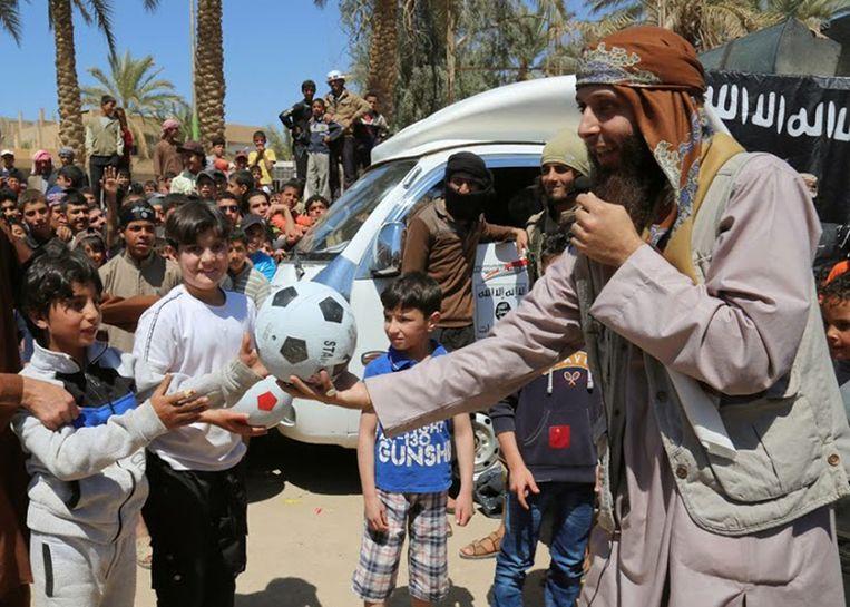 Een IS-strijder geeft een bal aan kinderen tijdens een evenement in Tel Abyad in Syrië. De foto is vrijgegeven door een website met IS- sympathieën en geverifieerd door persbureau AP.  Beeld AP