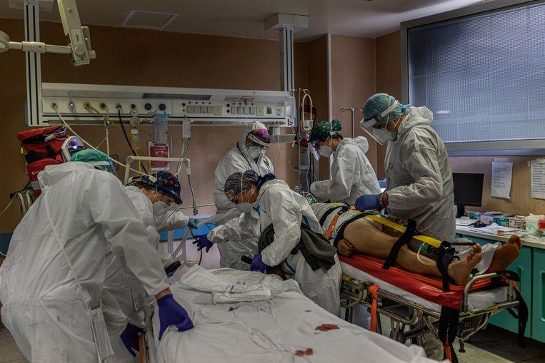 Artsen en verpleegkundigen behandelen in het Bolognini-ziekenhuis in Seriate vlakbij Bergamo een patiënt met ademhalingsproblemen. Beeld NYT/FABIO BUCCIARELLI