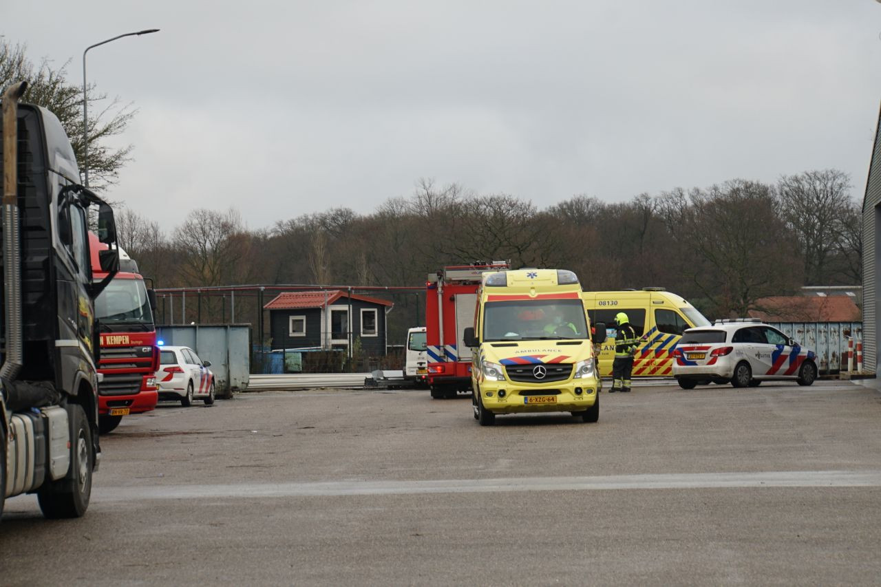 Brandweer en politie bij het truckservicebedrijf in Bergharen. Een monteur raakte bekneld onder een aanhangwagen tijdens het werk.