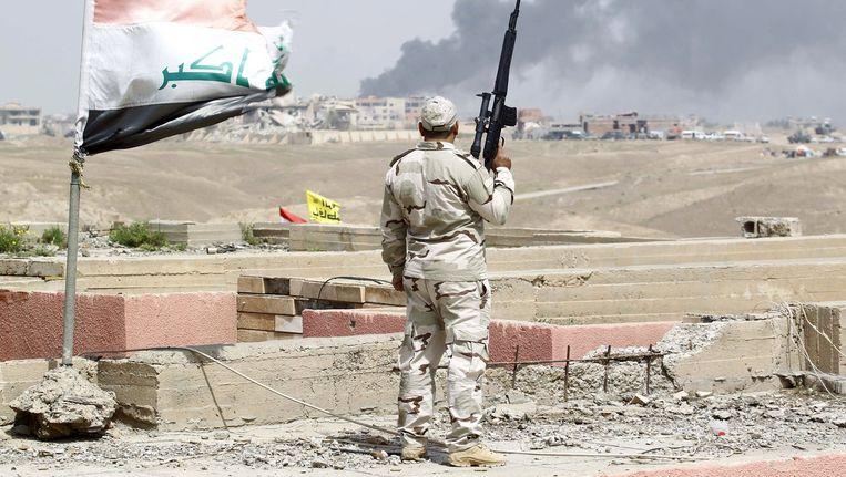 Een Iraakse soldaat kijkt naar de rook boven Tikrit. Beeld reuters