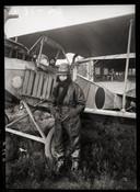 Een fotograaf van de Technische Dienst Luchtvaartafdeeling bij zijn vliegtuig.