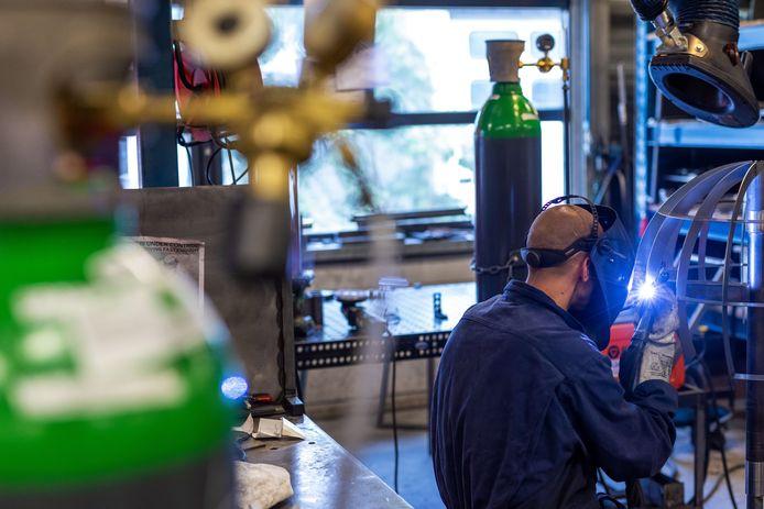 Een gedetineerden werkt aan een designlamp in de werkzaal metaalbewerking op het terrein van de PI Vught.