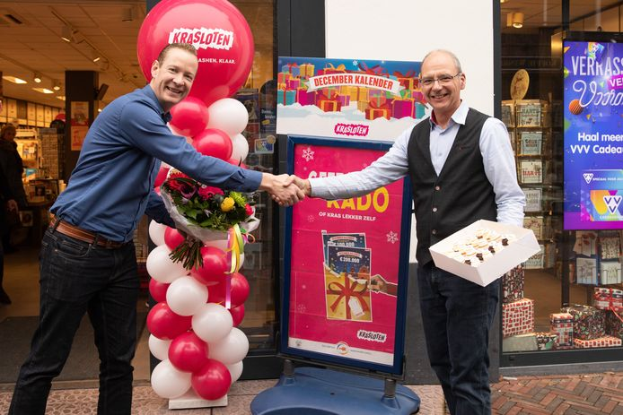 Rayonmanager Hans van Marion (donkerblauw shirt) van de Nederlandse Loterij kwam Bruna-eigenaar Robert Batenburg vanmiddag met bloemen feliciteren.