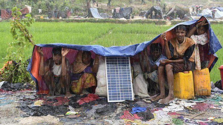 Vluchtelingen uit Myanmar, net aangekomen in het kamp Balukhali in Bangladesh, schuilen met hun spullen voor de moessonregen. Beeld AFP